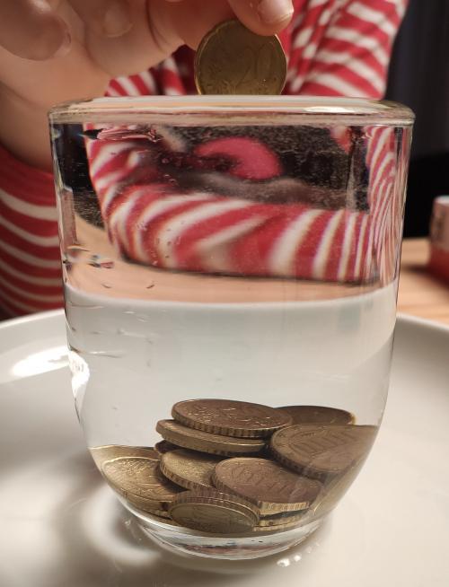 ¿Por qué si el vaso estaba lleno le ponemos monedas y el agua no se derrama?