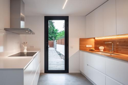 Cuina pràctica amb accés directe a l'exterior i llum natural. Detall de la placa de fusta de sobrecuina amb fusta natural.