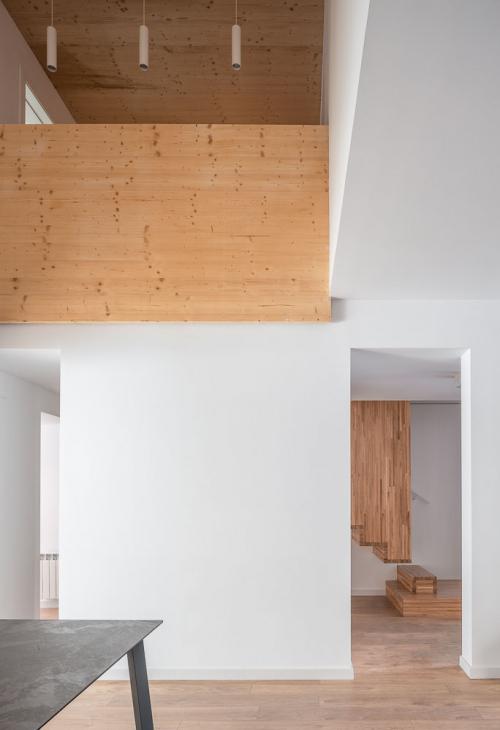 Doble espai en la sala d'estar - menjador amb la calidesa de la fusta com a acabat interior combinada amb l'elegància del blanc.