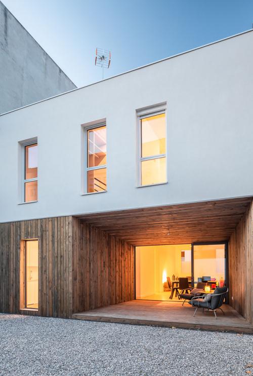 Façana vista des del pati exterior combinant l'acabat en fusta amb un arrebossat blanc.